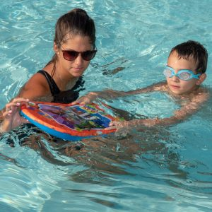 Woman and boy playing in pool